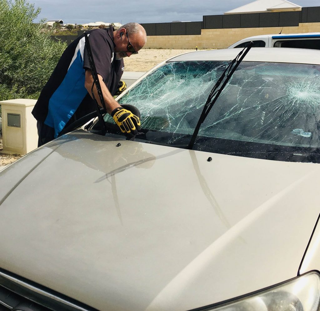 dave vacuuming excess glass from a windscreen crash